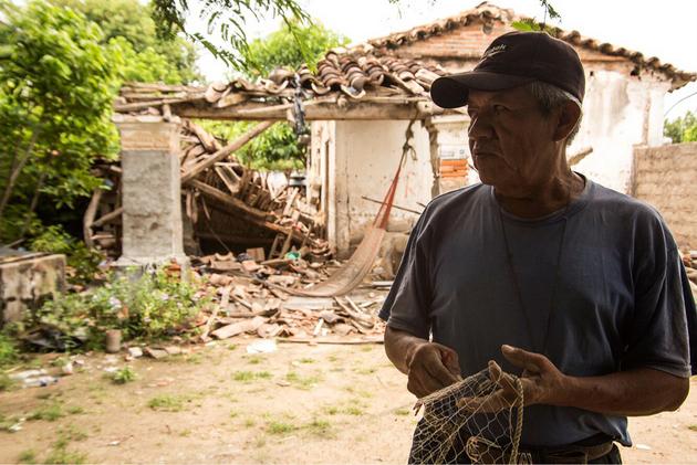 El pescador Heriberto Pineda Noriega, de 57 años, teje su red de pesca al lado de su casa destruida en el poblado costero de Huamuchil, en el municipio de San Dionisio del Mar Crédito: Diana Manzo/Pie de Página