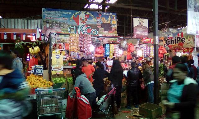 En Vega Central, principal mercado de frutas y verduras de Santiago, puestos de migrantes peruanos, 300.000 de los cuales viven en Chile, ofrecen productos frescos propios de su tierra, mientras en los alrededores se venden platillos típicos del vecino país. Crédito: Orlando Milesi/IPS