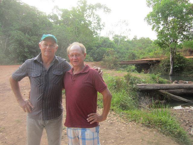 Los hermanos Daniel (izquierda) y Armando Schlindewein delante del pequeño puente sobre el riachuelo de Matrinxã, que quedará sumergido por la crecida del embalse de la central hidroeléctrica de Sinop, en Brasil. Como viven al otro lado, ambos se verán forzados a mudarse y las fincas de ambos, conectadas por el puente, quedarán separadas. Crédito: Mario Osava/IPS