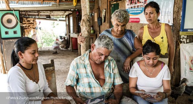 El agricultor Orlando Ruiz mientras y varias mujeres de su familia, mientras rememoran los duros tiempos como migrantes. Crédito: Patrick Zachmann/FAO
