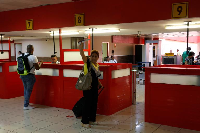 Una mujer hace un gesto de despedida momentos previos de abordar un vuelo en la terminal 3 del Aeropuerto Internacional José Martí, en La Habana, Cuba, en junio de 2017. Crédito: Jorge Luis Baños/IPS.