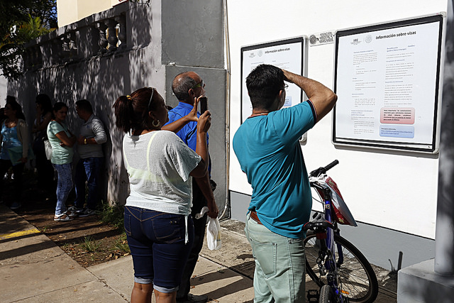 Un grupo de personas se informa sobre los trámites para obtener un visado para México, publicados en carteles en el exterior de la embajada de ese país en La Habana, la capital de Cuba. Crédito: Jorge Luis Baños/IPS