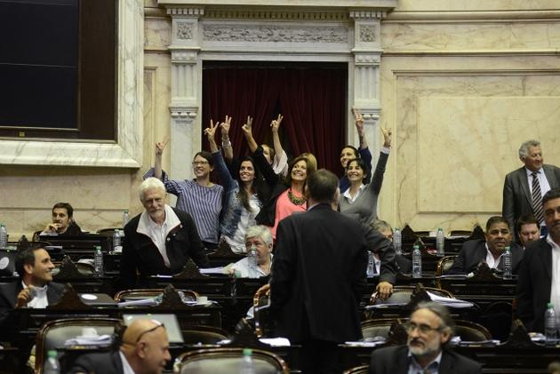 Un grupo de las diputadas que de madrugada y por sorpresa impusieron la aprobación de la ley de paridad de género en la representación política de Argentina, festejan con la señal de la victoria su logro al final de la histórica sesión. Crédito: Cámara de Diputados