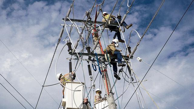 Trabajadores de una empresa de distribución eléctrica realizan tareas de mantenimiento de la red, en las afueras de San Salvador. Los países centroamericanos, incluido El Salvador, promueven un Corredor de Energías Limpias, para inyectar a su red interconectada de electricidad. Crédito: Edgardo Ayala/IPS