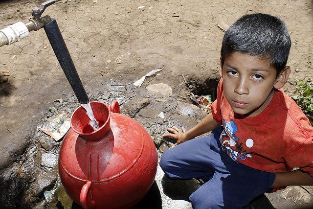 Un niño llena su cántaro de agua en una toma colectiva en Los Pinos, una comunidad del municipio de Tacuba, en el occidental departamento de Ahuachapán, en El Salvador. El acceso al agua potable en muchas comunidades rurales de América Central se mantiene como una carencia. Crédito: Edgardo Ayala/IPS