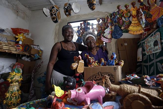 Maritza Arango y Margarita Montalvo integrantes del proyecto La muñeca negra posan para la foto en el interior de la habitación utilizada como taller de confecciones, en el municipio de La Lisa, La Habana, Cuba, en diciembre de 2017. Crédito: Jorge Luis Baños/IPS