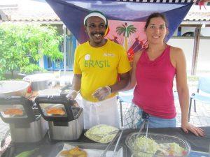 El productor cultural haitiano Bob Montinardy su esposa francesa, Melanie, en el quiosco de comida haitiana que regentan en la mensual feria de refugiados de la ciudad brasileña de Río de Janeiro, donde vive el matrimonio y sus dos hijos desde 2010 y donde ambos crearon la organización Mawon, de apoyo a los inmigrantes. Crédito: Mario Osava/IPS