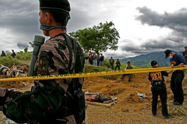 Un comando de la policía vigila mientras los investigadores desentierran a las víctimas de la masacre de Ampatuan. Crédito: InterAksyon