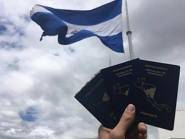 """Bajo una bandera de Nicaragua unos pasaportes de ese país, en cuya portada resalta la silueta del mapa centroamericano con la parte nicaragüense destacada. Su frontera sur, limítrofe con Costa Rica, se ha convertido en un """"muro de contención"""" de los migrantes que transitan desde América del Sur hacia el norte, para llegar a Estados Unidos. Crédito: José Adán Silva/IPS"""