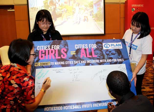 Alcaldes y activistas en el 9 Foro Urbano Mundial estampan su firma en una cartelera a favor de ciudades más seguras para nias, adolescentes y mujeres para 2030. Crédito: Manipadma Jena/IPS.