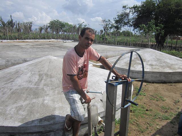 Abel Manto junto a sus cisternas que recogen agua de lluvia mediante una bomba manual que inventó para irrigar sus huertos. El uso de tecnologías como esta para captar y conservar ese recurso le permitieron desarrollar su finca, en el estado de Bahia, en un oasis en medio de la sequía que azota a la región del Semiárido, en el nordeste de Brasil. Crédito: Mario Osava/IPS