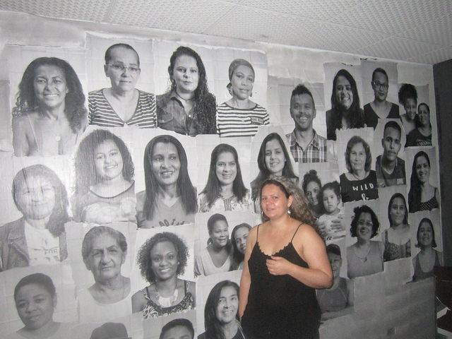 Cheila Patricia Souza, participante en la Ocupación São João 588, de un antiguo hotel convertido en vivienda para 80 familias, delante del mural con las fotos de los protagonistas de la lucha por tener un hogar propio, en el centro de la ciudad brasileña de São Paulo. La mayoría, como en batallas similares, son mujeres. Crédito: Mario Osava/IPS