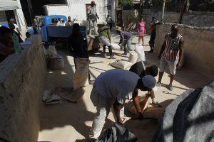 Varios hombres acarrean sacos con arena hacia un pequeño camión, en el patio de un establecimiento estatal que expende materiales de construcción en la capital de Cuba. Crédito: Jorge Luis Baños/IPS