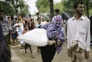 Una refugiada rohinyá carga con suministros humanitarios hasta su refugio improvisado. Crédito: Umer Aiman Khan/IPS.
