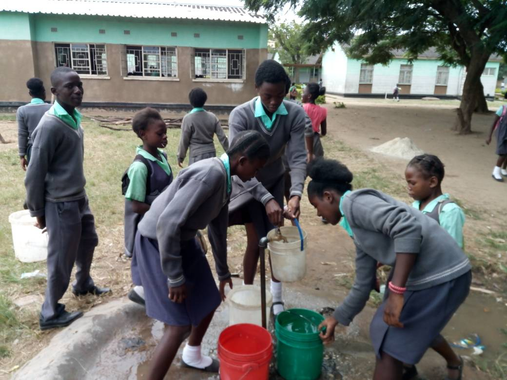 Estudiantes de la escuela primaria Matero East, en Zambia, recolectando agua. Crédito: Munich Advisors Group