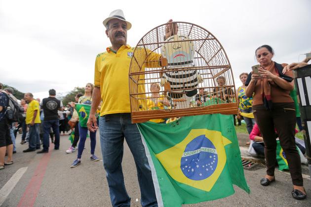 Un opositor al expresidente Luiz Inácio Lula da Silva sostiene una jaula con la imagen del dirigente izquierdista brasileño vestido de presidiario, durante una manifestación de sus detractores en Brasilia. Crédito: Fabio Rodrigues Pozzebom/Agência Brasil