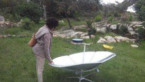 Una mujer joven admira una cocina solar parabólica en una feria solar realizara en Rusape, Zimbabwe. Crédito: Tonderayi Mukeredzi/IPS.