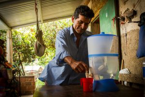 Tras una jornada laborando en la tierra donde cultiva maíz junto con frijol, Víctor de León se sirve un poco de agua recién purificada, uno de los beneficios del proyecto de adaptación al cambio climático en la región del Corredor Seco centroamericano, en el caserío de La Colmena, en el municipio de Candelaria de la Frontera, en el occidental departamento de San Ana, en El Salvador. Crédito: Edgardo Ayala/IPS