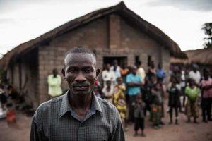 Un grupo de hombres , mujeres y niños desplazados se refugiaron en una iglesia en las afueras de la aldea de Nyunzu, en el este del Congo. Y Pastor Mbuyu (en primer plano) se ocupa de ellos. Crédito: Christian Jepsen/NRC.