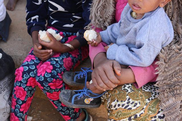 Un grupo de mujeres, niños y hombres eritreos, dejados cansados y sucios en un puesto de control para entrar a Etiopía, en la pequeña ciudad de Adinbried, a unos 50 kilómetros al sureste de Badme, tras cruzar la frontera la noche anterior. Crédito: James Jeffrey/IPS