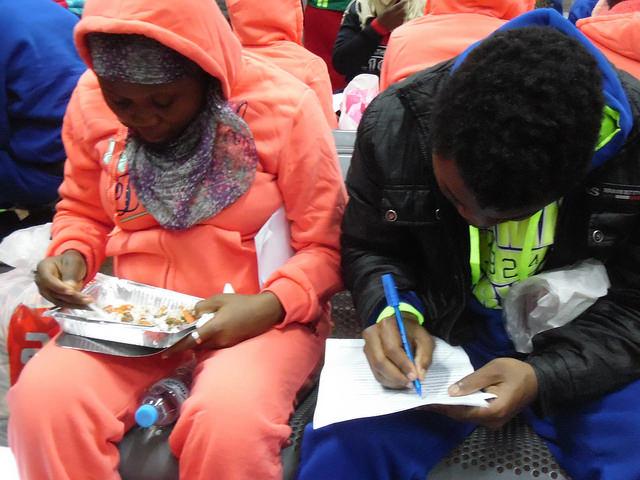 Emigrantes retornados comen algo mientras llenan papeles para la OIM en el aeropuerto de Nsimalen, en Yaundé, Camerún. Crédito: Mbom Sixtus/IPS.