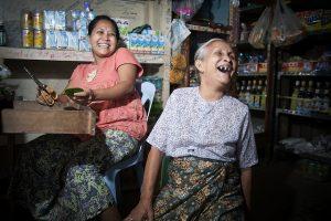 Una mujer de 70 años se ríe junto a su familia en una tienda de alimentos en Tachilek, Myanmar (Birmania). Crédito: Kibae Park/UN Photo.