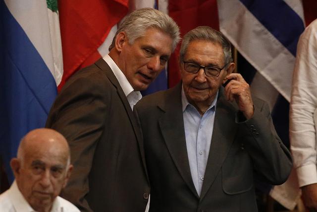 Miguel Díaz-Canel (c), presidente de Cuba, y su antecesor, el exmandatario Raúl Castro (d), actual primer secretario del Partido Comunista de Cuba, conversan durante la clausura del XXIV Encuentro del Foro de Sao Paulo, efectuado en el Palacio de Convenciones de La Habana. Crédito: Jorge Luis Baños/IPS