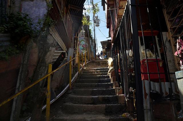 Una pareja joven al fondo de una empinada escalera de La Carpio, un barrio degradado de la periferia de San José de Costa Rica. Alrededor de la mitad de los jóvenes que viven en comunidades como esta de América Central dicen que migrarían si pudieran. Crédito: Josué Sequeira/IPS