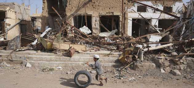 Un niño corre con una llanta frente a edificios destruidos por ataques aéreos en la Ciudad Vieja. Según Unicef, los centros de salud se redujeron a la mitad en el país, miles de escuelas quedaron destruidas y más de 2.000 niños murieron. Crédito: Giles Clarke/OCHA