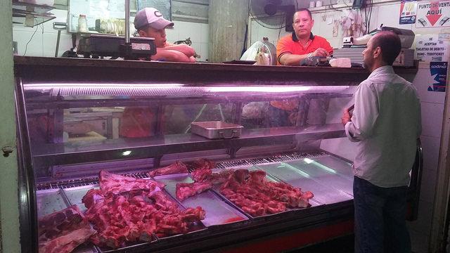 El dueño y el vendedor de una carnicería poco abastecida conversan en un barrio del centro de Caracas sobre la crítica situación en Venezuela con un cliente habitual, quien no compró nada por falta de dinero para ello. La escasez y la carestía atosigan de manera creciente a los venezolanos. Crédito: Humberto Márquez/IPS