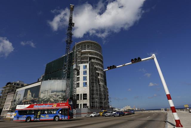 Un bus turístico pasa ante el edificio en construcción del Hotel Prado y Malecón, un proyecto conjunto del Grupo cubano de Turismo Gaviota y la empresa francesa Accor, en un lugar emblemático de La Habana. El crecimiento del turismo es una de las apuestas del gobierno para dinamizar la alicaída economía del país. Crédito: Jorge Luis Baños/IPS