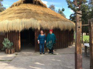 Juana Cheuquepan (I) y su madre, la machi (chamán) María Colipe, en la puerta de la ruca de la Asociación Kiñe Pu Liwen, en el municipio La Pintana, en la periferia sur de Santiago, donde los mapuches que residen en el área metropolitana de la capital de Chile celebran ceremonias y reuniones. Crédito: Orlando Milesi/IPS