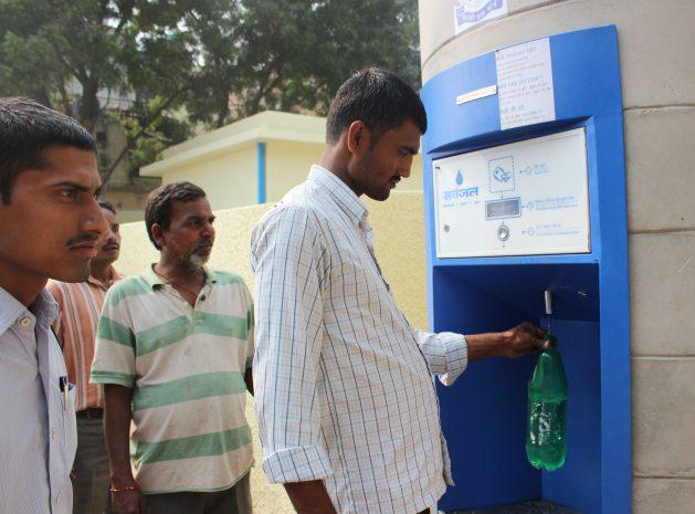 Un hombre saca agua de un dispensador automático, que funciona con energía solar, en el asentamiento irregular de Savda Ghevra, en Nueva Delhi. Gracia a esas máquinas, que funcionan con tarjetas recargables, disminuyeron las enfermedades derivadas del agua contaminada. Crédito: Ranjit Devraj/IPS