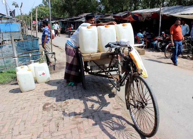 En la localidad costera de Satkhira, en el sudoeste de Bangladesh, donde las fuentes de agua dulce sufren la intrusión de agua salada, un vendedor de agua llena tanques de 20 litros en cañerías públicas para vender en islas donde las familias destinan unos 300 takas (3,59 dólares) al mes para comprar agua potable para beber y cocinar. Crédito: Manipadma Jena/IPS.