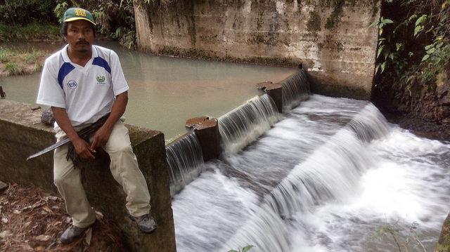 Juan Benítez, presidente de la Asociación Nuevos Horizontes de La Joya de Talchiga, descansa en el borde del dique construido como parte de la Minicentral Hidroeléctrica El Calambre. Las pocas más de 40 familias del caserío tienen electricidad desde 2012, gracias al proyecto construido por ellos mismos, en las montañas del este de El Salvador.Crédito: Edgardo Ayala/IPS