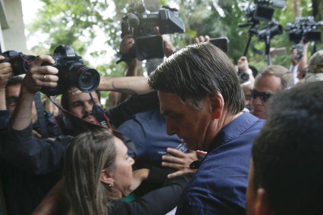 Jair Bolsonaro, el exmilitar de extrema derecha que ganó con contundencia la primera vuelta de las elecciones presidenciales en Brasil, entre fotógrafos y adeptos entusiastas cuando se dirigía a votar el domingo 7, en Río de Janeiro. Crédito: Tânia Rêgo/Agência Brasil-Fotos Públicas