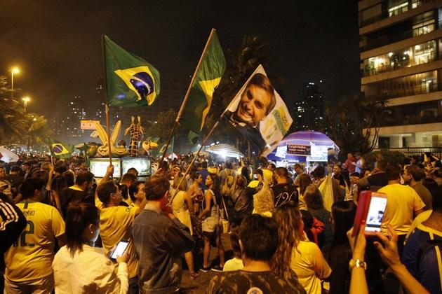 Partidarios del presidente electo, Jair Bolsonaro, festejan su triunfo la madrugada del 29 de octubre, delante de la residencia del excapitán, en el oeste de Río de Janeiro. El candidato de extrema derecha obtuvo 55,13 por ciento del total de votos válidos comenzará sus cuatro años de presidencia el 1 de enero de 2019. Crédito: Fernando Frazão/Agencia Brasil
