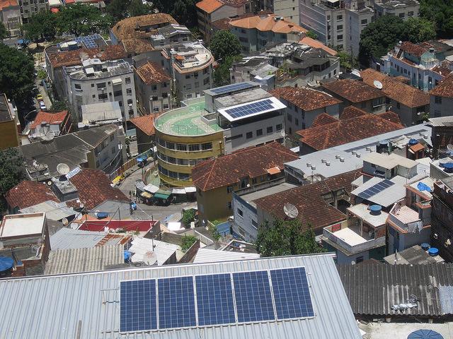 Paneles fotovoltaicos instalados en tres edificios del barrio pobre y empinado del Morro de Santa Marta, en Río de Janeiro. En el medio, la Guardería CEPAC, que redujo 80 por ciento de sus gastos con esta energía, con una terraza verde y dos conjuntos de paneles. Crédito: Mario Osava/IPS