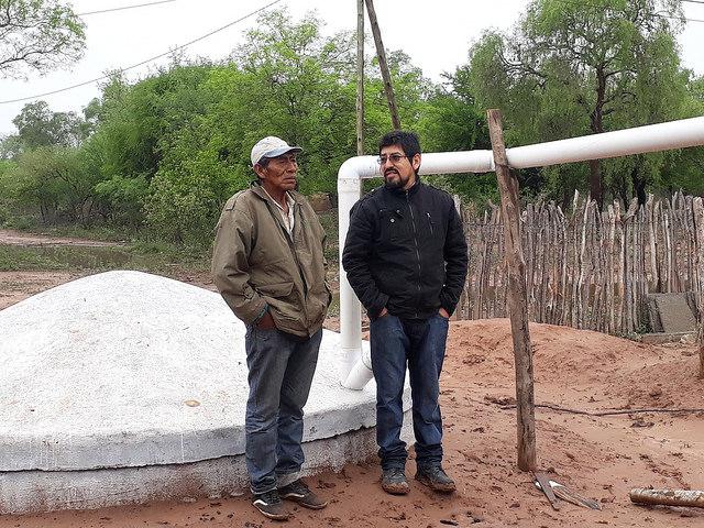 El wichí Mariano Barraza (I), junto a Enzo Romero, técnico de la organización Fundapaz, junto a la cisterna construida para almacenar agua de lluvia en la comunidad indígena de Lote 6, para enfrentar los seis meses de sequía que soporta cada año esta zona de la provincia de Salta, en el Chaco, en el norte de Argentina. Crédito: Daniel Gutman/IPS