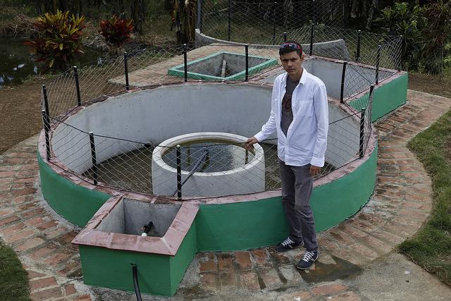 El ingeniero de 32 años Alexander López Savrán, creador del biodigestor de cúpula fija estándar que permite crear redes de distribución a partir de materiales fácilmente disponibles en Cuba, ante uno de estos sistemas en la localidad rural La Macuca, en Cabaiguán, en Cuba. Crédito: Jorge Luis Baños/IPS