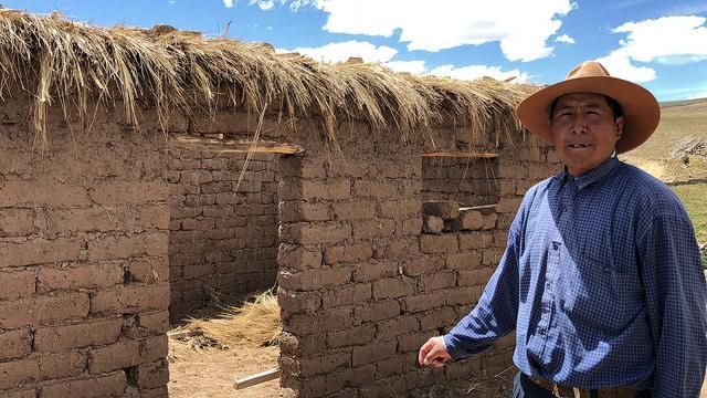 Néstor Flores, un comunero de Quinsalakaya, a más de 4.300 metros de altura, en las alturas andinas, en el sureste de Perú, muestra la estructura con muros de ladrillos de adobe de su nueva vivienda abrigadora, a la que él y su familia se trasladarán antes de finalizar el año y que les permitirá vivir libres de frío y de humo. Crédito: Annie Solís/IPS