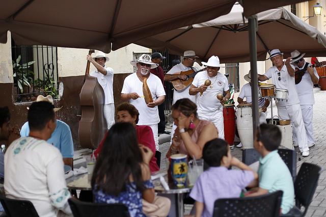 Un grupo de música tradicional cubana ameniza la terraza de un establecimiento estatal que ofrece servicios de gastronomía al turismo internacional, en un una calle de La Habana Vieja, en Cuba. Crédito: Jorge Luis Baños/IPS