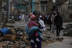 Una mujer camina con un bebe en sus brazos, entre los escombros dejados en el municipio de 10 de Octubre, uno de los que conforman La Habana, después que la capital cubana fuese azotada por un violento tornado la noche del 27 de enero. Crédito: Jorge Luis Baños/IPS