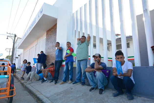 Migrantes hacen fila para ser atendidos en la sede del Instituto Nacional de Migración en Tenosique, en la frontera mexicana con Guatemala. Crédito: Jaime Ávalos/En el Camino