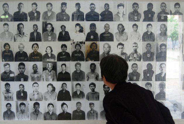 Un turista observa las fotografías de las personas que murieron durante el régimen del Jemer Rojo. Crédito: Robert Carmichael/IPS.