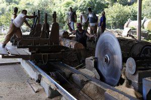 Trabajadores sierran troncos con maquinaria obsoleta en El Aserrío, la pequeña y centenaria planta procesadora de la estatal Empresa Agroforestal Guamá, en el municipio montañoso de Guamá, en la provincia de Santiago de Cuba, en el este del país insular caribeño. Crédito: Jorge Luis Baños/IPS https://c2.staticflickr.com/8/7927/33208291618_9294326580_o.jpg