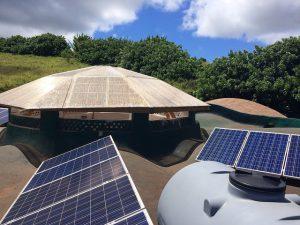 El techo de la original sede de la Fundación Toki en la Isla de Pascua o Rapa Nui, situada a 3.800 kilómetros de las costas chilenas, cumple la doble función de recuperar el agua lluvia la cual se conduce a ocho grandes estanques de acumulación y de generar energía eléctrica mediante seis paneles solares. Crédito: Orlando Milesi/IPS