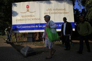 """Algunos viandantes pasan junto a un gran cartel donde destaca el lema """"Reforma constitucional, mi voluntad, mi Constitución"""", en que se promueve la participación en el referendo sobre el texto de la nueva Constitución, que se realizará en Cuba el domingo 24 de febrero. Crédito: Jorge Luis Baños/IPS"""