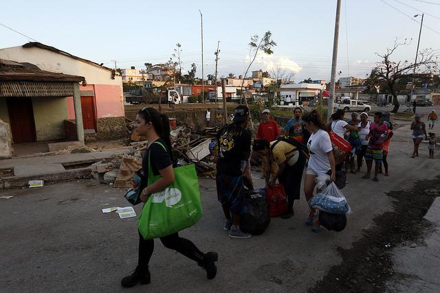 A comienzos de febrero, un grupo de voluntarios que se organizaron para atender a los damnificados del tornado que azotó La Habana el 27 de enero, camina cargado de bolsas con diversos bienes donados para brindar asistencia a las personas necesitadas, en uno el municipio de Regla, uno de los que conforman la capital de Cuba. Crédito: Jorge Luis Baños/IPS