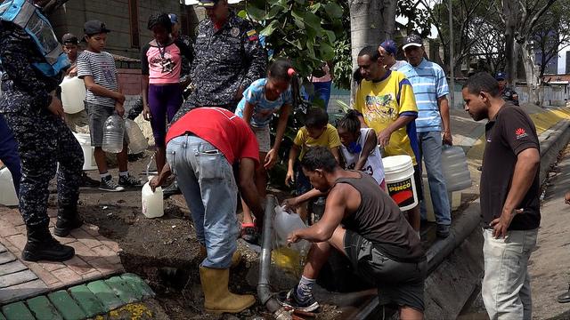 Habitantes del barrio de San Agustín, en el centro de Caracas, recogen agua de una tubería que pasa junto a la principal autopista de la capital de Venezuela, para después acarrearla a sus hogares por las empinadas escaleras que les conducen a ellas desde la avenida. La ausencia de electricidad por entre cuatro y ocho días, incremento las penurias crónicas con el recurso de amplios sectores de la población. Crédito: Humberto Márquez/IPS